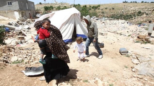 عائلة فلسطينية تم هدم منزلها من قبل جرافات إسرائيلية تمر أمام خيمة في 21 ابريل، 2015 في قرية الديرات جنوبي الضفة الغربية. (Hazem Bader/AFP)
