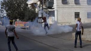 شبان فلسطينيون ملثمون يلقون قنابل غاز باتجاه عناصر شرطة الحدود خلال اشتباكات في بلدة الرام في الضفة الغربية، 22 اكتوبر 2015 (AFP Photo/Abbas Momani)