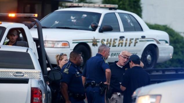 عناصر شرطة امريكية امام سيارة شرطة باتون روج في موقع مقتل ثلاثة عناصر شرطة في الصباح، 17 يوليو 2016 (Sean Gardner/Getty Images/AFP)