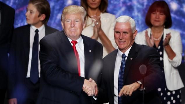 المرشح الجمهوري للرئاسة دونالد ترامب (من اليسار) يصافح المرشح الجمهوري لمنصب نائب الرئيس مايك بنس في ختام المؤتمر العام للحزب الجمهوري في 21 يوليو، 2016 في صالة 'كويكن لونز أرينا' في كليفلاند بولاية أوهايو. (Alex Wong/Getty Images/AFP)