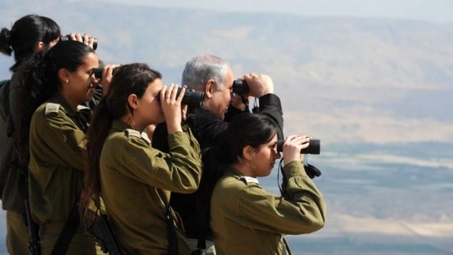 رئيس الوزراء بينيامين نتنياهو ينظر إلى غور الأردن مع جنديات إسرائيليات خلال جولة في 2011. (Moshe Milner/GPO/Flash90)