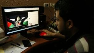 """صورة توضيحية: شاب فلسطيني من غزة ينظر إلى تدوينة مؤيدة للفلسطينيين على موقع """"فيسبوك""""، 7 أبريل، 2013. (Abed Rahim Khatib / Flash90)"""
