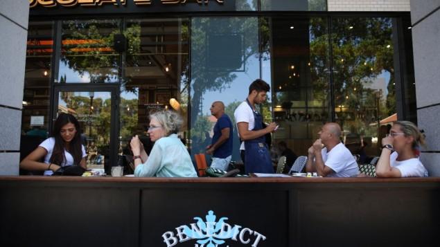 إسرائيليون يتناولون الطعام في مطعم 'بنديكتز' في مجمع 'سارونا' التجاري وسط تل أبيب، 9 يونيو، 2016، في صباح اليوم الذي تلا الهجوم الدامي في الموقع. (Miriam Alster/Flash90)