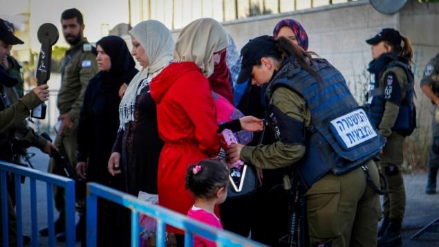 فلسطينيون يخضعون لتفتيش أمني عند حاجز في مدينة بيت لحم في الضفة الغربية، خلال توجههم إلى المسجد الأقصى في القدس للمشاركة في صلاة الجمعة الأولى من شهر رمضان، 10 يونيو، 2016. (Wisam Hashlamoun/Flash90)