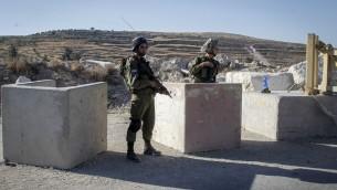جنود إسرائيليون يضعون حاجزا بالقرب من مدينة الخليل في الضفة الغربية، 2 يوليو 2016 (Wisam Hashlamoun/Flash90)