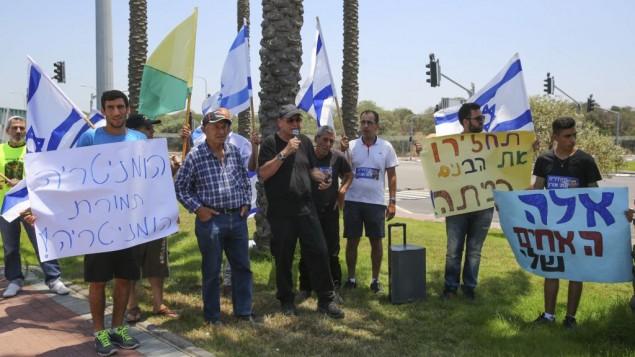 أصدقاء وعائلة الجندي الإسرائيلي الذي لا تزال حماس تحتجز رفاته في غزة يتظاهرون خارج ميناء أشدود جنوبي إسرائيل في 3 يوليو، 2016، مع وصول 'ليدي ليلى'، سفينة تركية تحمل المساعدات إلى القطاع. (Flash90)