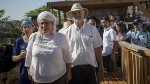 والدا هاليل يافا أريئيل، التي قُتلت في هجوم طعن في كريات أربع، ومئات المناصرين يصلون إلى الحرم القدسي في البلدة القديمة يوم الثلاثاء، 12 يوليو، 2016. (Yonatan Sindel/Flash90)