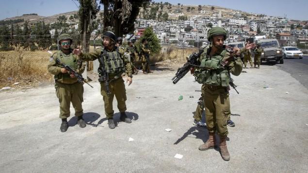 جنود اسرائيليون في موقع طعن جنديين من قبل فلسطينيا في مفرق العروب في الضفة الغربية، 18 يوليو 2016 (Wisam Hashlamoun/Flash90)