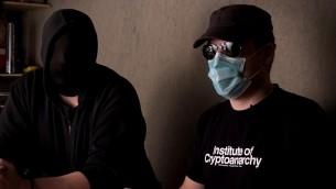 فوضويون تشفير ملثمون يتحدثون مع يوفال اور في مشهد من فيلم 'في لب الشبكة العميقة المظلمة' (Courtesy)