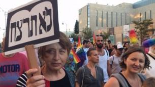 سيدة تحمل لافتة كُتب عليها 'لا تقتل'، في موكب الفخر للمثليين في 21 يوليو، 2016. (تايمز أوف إسرائيل)