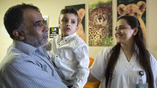 Ahmad Dawabsha, the sole survivor of a West Bank arson attack in Duma village, is carried by his grandfather Hussein at the Tel HaShomer Hospital in the city of Ramat Gan, Israel, Friday, July 22, 2016. AP Photo/Tsafrir Abayov