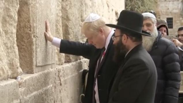 بوريس جونسون خلال في باحة الحائط الغربي خلال زيارة قام بها إلى إسرائيل عندما كان رئيسا لبلدية لندن، نوفمبر 2015. (Guardian screenshot)