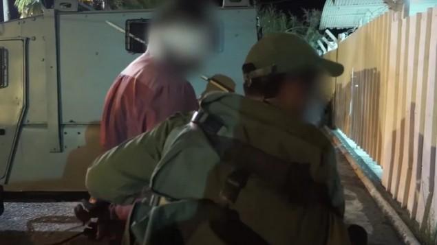 الجيش الإسرائيلي يعتقل رجلا خلال مداهمة في الضفة الغربية لإعتقال أعضاء خلية تابعة لحركة حماس تقف وراء قتل الحاخام ميكي مارك، 27 يوليو، 2016. (لقطة شاشة: YouTube)