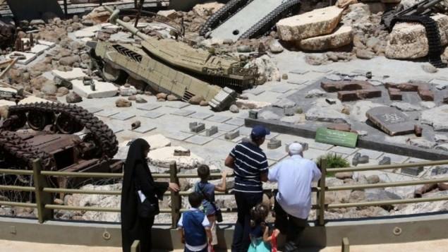 """زوار يتفرجون على دبابات تركها الجيش الإسرائيلي في لبنان خلال زيارتهم لمتحف """"المعلم السياحي للمقاومة"""" الذي يديره حزب الله في مليتا، جنوب لبنان، 12 يوليو، 2016. (AFP PHOTO / MAHMOUD ZAYYAT)"""