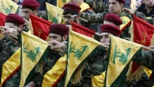عناصر من منظمة حزب الله يحملون الأعلام خلال جنازة أحد مقاتلي المنظمة، الذي قُتل خلال قتاله إلى جانب قوات النظام السوري في سوريا، 1 مارس، 2016. (AFP/MAHMOUD ZAYYAT)