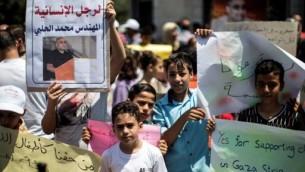 أطفال فلسطينيون يحملون صورا لمحمد الحلبي (من اليسار)، مدير فرع 'وورلد فيجين' في غزة، منظمة غير حكومية مقرها في الولايات المتحدة، خلال احتجاج تضامني معه في مدينة غزة في 7 أغسطس، 2016. (AFP PHOTO / MAHMUD HAMS)