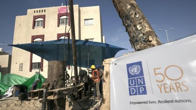 عمال بناء فلسطينيين يعملون على بئر مياه في مشروع إسكان ممول من السعودية ويتم تنفيذه من قبل برنامج الأمم المتحدة الإنمائي (UNDP)، في رفح جنوبي قطاع غزة، 9 أغسطس، 2016. (AFP Photo/Said Khatib)