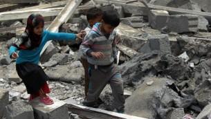 اطفال يمنيون وسط حطام منزل في صنعاء، اليمن، 11 اغسطس 2016 (MOHAMMED HUWAIS / AFP)