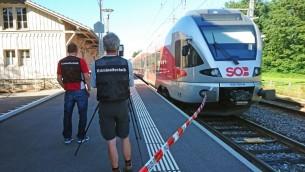 عناصر الشرطة السويسرية يقفون امام قطار بعد ان اشعل رجل النيران به وقام بطعن مسافرين، 13 أغسطس 2016 (BEAT KAELIN / NEWSPICTURES.CH / AFP)