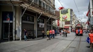 اشخاص يمرون امام محلات مقفلة في جادة الاستقلال في إسطنبول، 12 أغسطس (OZAN KOSE / AFP)