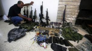 احد عناصر قوات الامن الفلسطينية يعرض اسلحة في محطة شرطة في الضفة الغربية، عثرت عليها قوات الشرطة خلال عملية البحث عن مسلحين فارين من العدالة، 21 اغسطس 2016 (AFP/JAAFAR ASHTIYEH)
