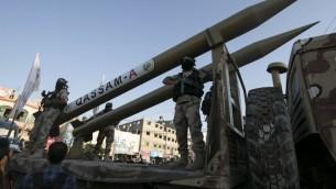 اعضاء في كتائب عز الدين القسام، الجناح العسكري لحركة حماس، يعرضون صواريخ قسام من صناعة محلية خلال موكب عسكري معادي لإسرائيل في الذكرى الثانية لمقتل القادة العسكريين لحماس محمد ابو شمالة ورائد العطار، 21 اغسطس 2016 (AFP / SAID KHATIB)