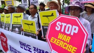 متظاهرن يرفعون لافتات ضد التدريبات العسكرية الامريكية الكورية الجنوبية المشتركة امام السفارة الامريكية في سيول، 22 اغسطس 2016 (JUNG YEON-JE / AFP)