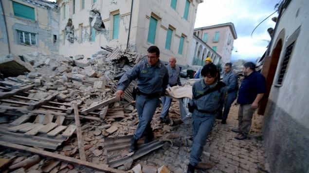 منقذون يحملون رجلا من بين الأنقاض بعد أن ضرب زلزال قوي بلدة أماتريتشي الإيطالية في 24 أغسطس، 2016. (AFP PHOTO / FILIPPO MONTEFORTE)