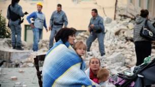 ضحايا يجلسون بين أنقاض منزل مدمر بعد أن ضرب زلزال قوي بلدة أماتريتشي الإيطالية في 24 أغسطس، 2016. (AFP PHOTO / FILIPPO MONTEFORTE)