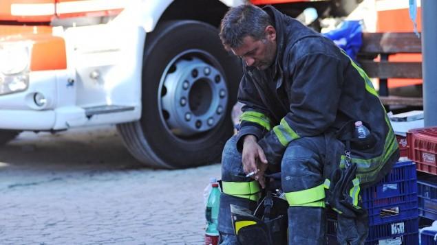 رجل اطفاء يستريح في بلدة اماتريتشي في مركز ايطاليا، بعد ان هز زلزال بقوة 6,2 ايطاليا، 24 اغسطس 2016 (AFP PHOTO/MARCO ZEPPETELLA)
