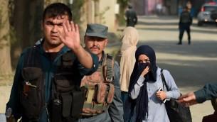 الشرطة الافغانية تواكب طالبة كانت عالقة داخل حرم الجامعة الامريكية في كابول بعد هجوم استمر 10 ساعات، 24 اغسطس 2016 (WAKIL KOHSAR / AFP)