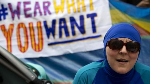 """إمرأة ترتدي """"البوركيني"""" تنضم إلى احتجاج أمام السفارة الفرنسية في لندن في 25 أغسطس، 2016،  خلال تظاهرة تحت عنوان """"حفلة الشاطئ ارتدي ما تريدين""""  للإحتجاج على حظر البوركيني على الشواطئ الفرنسية وإظهار التضامن مع النساء المسلمات.  (AFP PHOTO / JUSTIN TALLIS)"""