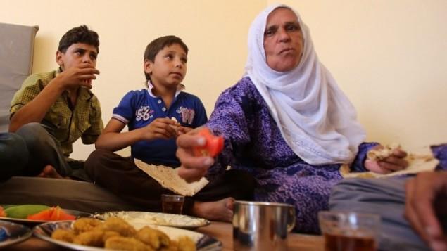 غائلة سورية تم اخلائها من بلدة داريا تتنناول وجبة الفطور في مركز اقامة مؤقت في بلدة حرجلة التي تحت سيطرة النظام، 27 اغسطس 2016 (AFP/Youssef KARWASHAN)