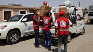 موظفو الهلال الاحمر السوري يوزعون رزم مساعدات في مركز اقامة مؤقت في بلدة حرجلة التي تحت سيطرة النظام، 27 اغسطس 2016 (AFP/Youssef KARWASHAN)