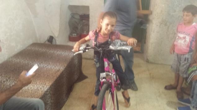 أنوار برقان، طقلة فلسطيينة تبلغ من العمر 8 أعوام قام عنصران من شرطة حرس الحدود الإسرائيل بتدمير دراجتها، تحرب دراجتها الجديدة التي قام رجل إسرائيلي بالتبرع بها، 17 أغسطس، 2016. (Lonny Baskin)