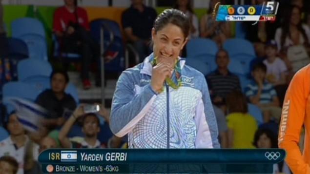 لاعبة الجودو الإسرائيلية ياردين جربي تعض بمزاح ميداليتها البرونزية خلال حفل توزيع الجوائز في الالعاب الاولمبية في ريو، 9 اغسطس 2016 (screen capture: Channel 55)