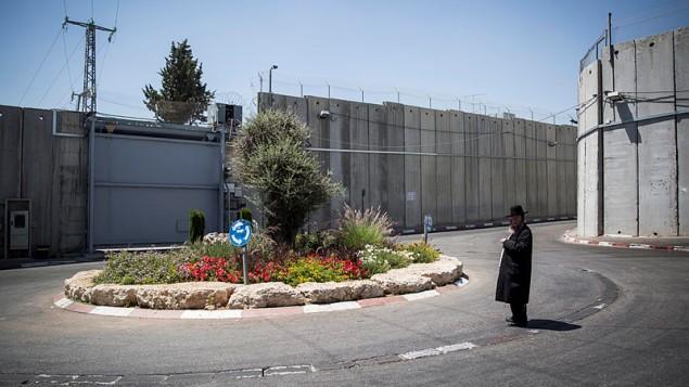 صورة توضيحية: رجل حريدي يقف عند تقاطع طرق بالقرب من مدخل موقع 'قبر راحيل' المقدس، المحاط بجدار فصل، بالقرب من بيت لحم، 26 يونيو، 2014. (Hadas Parush/Flash90)