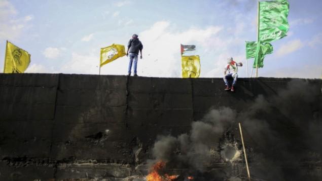أعلام فتح وحماس وحركات فلسطينية أخرى فوق الجدار الفاصل في الضفة الغربية خلال تظاهرة احتجاجية في نوفمبر 2015. (صورة توضيحية: Muammar Awad/FLASH90)
