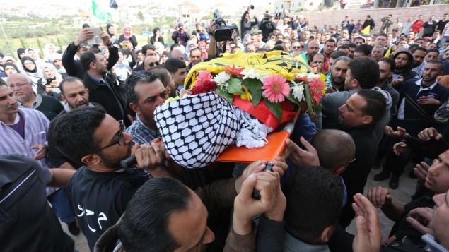 مشيعون فلسطينيون يهتفون شعارات خلال حملهم لجثمان محمود شعلان (17 عاما) خلال جنازته في قرية دير دبوان، بالقرب من مدينة رام الله في الضفة الغربية، 2 مارس، 2016. (Photo by Flash90)