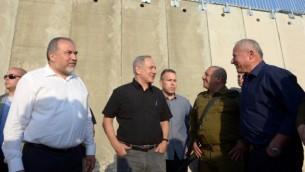 رئيس الوزراء بينيامين نتنياهو ووزير الدفاع أفيغدور ليبرمان إلى جانب عضو الكنيست أفي ديختر ورئيس هيئة  الأركان العامة للجيش الإسرائيلي غادي آيزنكوت، خلال زيارة للجدار الجديد بين إسرائيل والضفة الغربية بالقرب من بلدة ترقوميا، 20 يوليو، 2016. (Haim Zach/GPO)