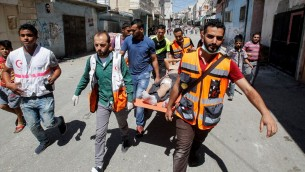 مشعفون يخلون فلسطينيا اصيب خلال اشتباكات مع الجيش الإسرائيلي في مخيم الفوار جنوب الخليل، 16 اغسطس 2016 (Wisam Hashlamoun/Flash90)