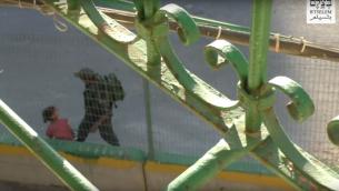 لقطة شاشة من فيديو اصدرته جمعية بتسيلم يظهر شرطي حدود يأخد دراجة طفلة فلسطينية تبلغ 8 سنوات ويرميها بين الاشجار، 25 يوليو 2016 (Screen capture: B'Tselem)