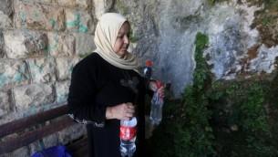 سيدة من عائلة سليم تحمل المياه المملوءة بمياه نبع في 23 يونيو، 2016 في بلدة سلفيت، شمال رام الله. (AFP PHOTO / JAAFAR ASHTIYEH)