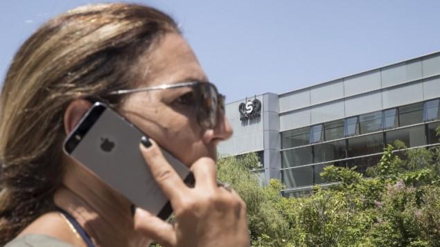 امرأة اسرائيلية تستخدم جهاز الآيفون الخاص بها امام مبنى شركة الامن الرقمي الإسرائيلية مجموعة NSO في هرتسليا، 28 اغسطس 2016 (AFP Photo/Jack Guez)