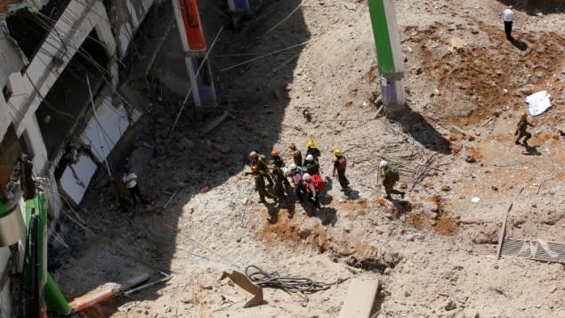 مسعفون ووحدات طوارئ يخلون شخص مصاب في موقع بناء حيث انهار موقف سيارات تحت ارضي في حي رمات هحايال في تل ابيب، 5 سبتمبر 2016 (AFP PHOTO / GIL COHEN-MAGEN)