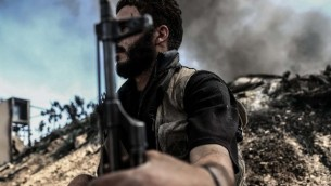 """مقاتل من """"جيش الإسلام"""" يجلس القرب من نيران تتصاعد على خط المواجهة، التي يستخدمها المقاتلون للإحتماء، في قرية تل الصوان في منطقة دوما التي تعتبر معقلا للمتمردين، في ريف دمشق، 5 سبتمبر،  2016.  (AFP PHOTO / Sameer Al-Doumy)"""