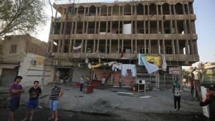 عراقيون يقفون امام مبنى تضرر نتيجة تفجير سيارة مفخخة في حي الكرادة، بغداد، 6 سبتمبر 2016 (AHMAD AL-RUBAYE / AFP)
