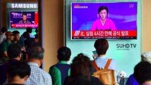 أشخاص يشاهدون بث إخباري تلفزيوني يظهر مذيعة التلفزيون الكوري الشمالي تعلن عن التجربة النووية الأخيرة التي أجرتها البلاد، في محطة للقطارات في سول، 9 سبتمبر، 2016. (AFP PHOTO / JUNG YEON-JE)