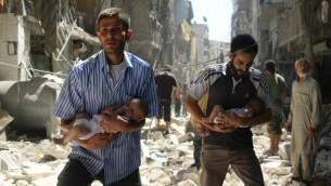 رجال سوريون يحملون اطفال يمرون بين الحطام بعد غارات جوية في مدينة حلب السورية، 11 سبتمبر 2016 (Ameer Alhalbi/AFP)