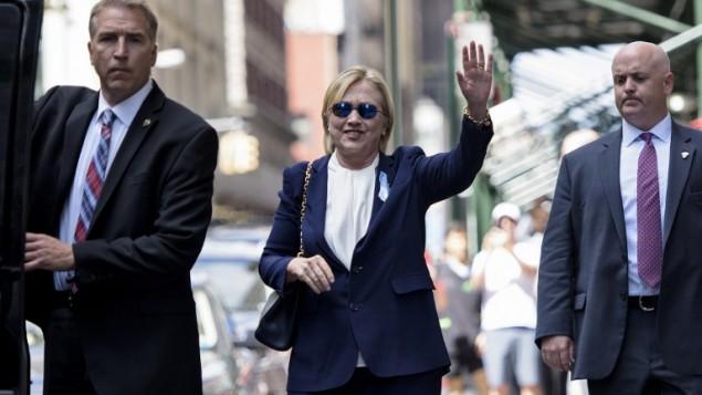 المرشحة الديمقراطية للانتخابات الامريكية هيلاري كلينتون تلوح للصحافة عند مغادرتها سقة ابنتها بعد ان استراحت هناك، 11 سبتمبر 2016 (BRENDAN SMIALOWSKI / AFP)